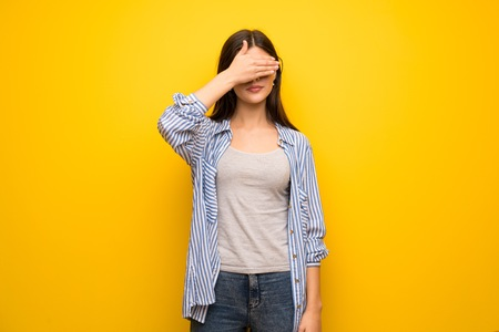 Teenager girl over yellow wall covering eyes by hands. Do not want to see something Stock Photo