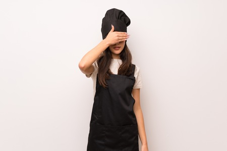 Teenager chef  over white wall covering eyes by hands. Do not want to see something