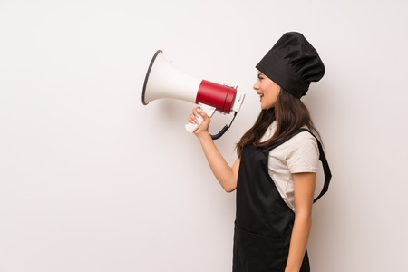 Teenager chef  over white wall shouting through a megaphone Imagens