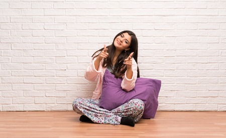 Teenager girl in pajamas pointing to the front and smiling