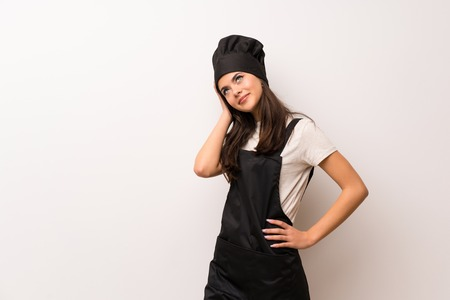 Teenager chef  over white wall thinking an idea while scratching head