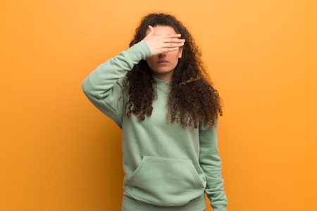 Teenager girl over ocher wall covering eyes by hands. Do not want to see something
