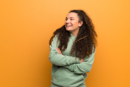 Teenager girl over ocher wall happy and smiling