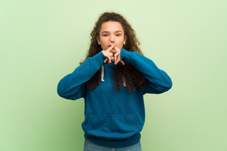 Teenager girl over green wall showing a sign of silence gesture Stock Photo