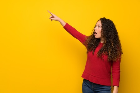 Teenager girl with red sweater over yellow wall pointing away Reklamní fotografie
