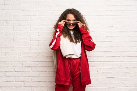Teenager sport girl with curly hair with glasses and surprised