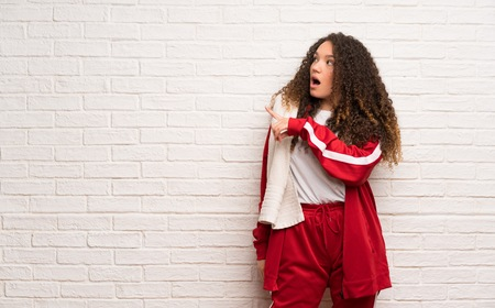 Teenager sport girl with curly hair surprised and pointing side