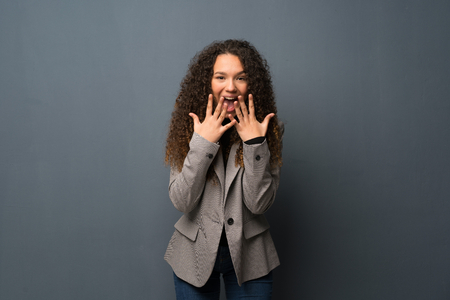 Teenager girl over blue wall with surprise facial expression