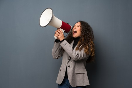 Teenager girl over blue wall shouting through a megaphone