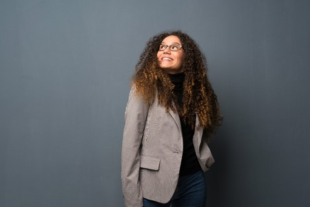 Teenager girl over blue wall with glasses and smiling Фото со стока