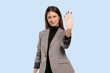 Business woman happy and counting four with fingers over isolated blue background Фото со стока