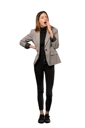 A full-length shot of a Business woman yawning and covering wide open mouth with hand over isolated white background