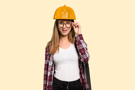 Architect woman with glasses and surprised over isolated yellow background