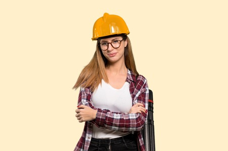 Architect woman with glasses and smiling over isolated yellow background