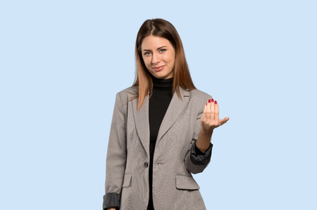 Business woman inviting to come with hand. Happy that you came over isolated blue background