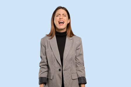 Business woman shouting to the front with mouth wide open over isolated blue background