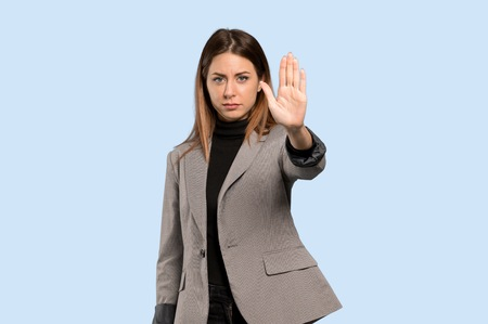 Business woman making stop gesture denying a situation that thinks wrong over isolated blue background