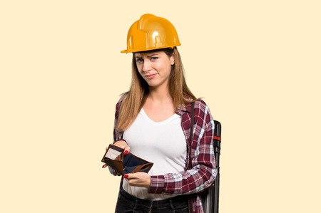 Architect woman holding a wallet over isolated yellow background
