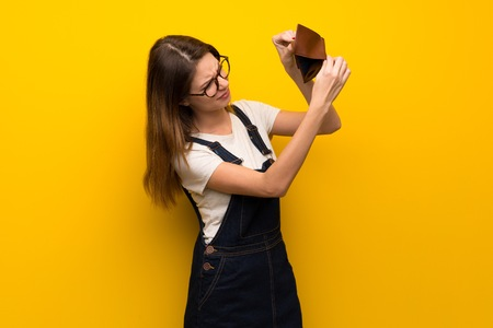 Woman over yellow wall holding a wallet