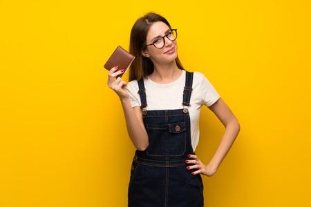 Frau über gelber Wand, die eine Brieftasche hält