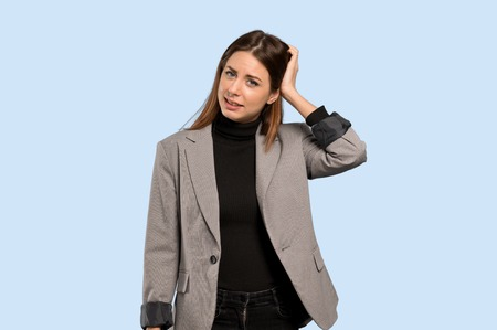 Business woman with an expression of frustration and not understanding over isolated blue background