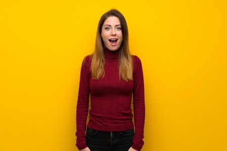 Woman with turtleneck over yellow wall with surprise facial expression