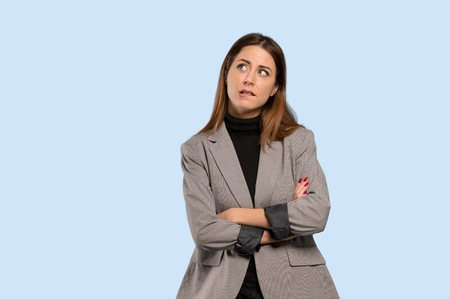 Business woman with confuse face expression while bites lip over isolated blue background