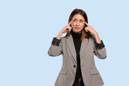 Business woman having doubts and thinking over isolated blue background