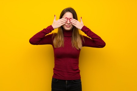 Woman with turtleneck over yellow wall covering eyes by hands. Surprised to see what is ahead