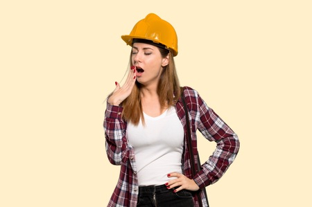Architect woman yawning and covering wide open mouth with hand over isolated yellow background Stock Photo