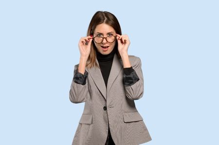 Business woman with glasses and surprised over isolated blue background Фото со стока