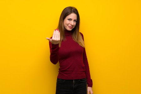 Woman with turtleneck over yellow wall inviting to come with hand. Happy that you came Standard-Bild