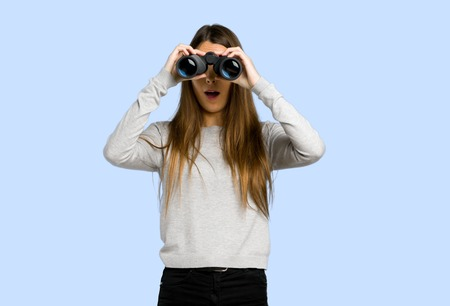 young girl and looking in the distance with binoculars on blue background