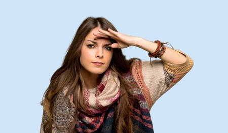 Young hippie woman looking far away with hand to look something over isolated blue background