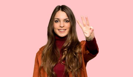 Young woman with coat happy and counting three with fingers over isolated pink background