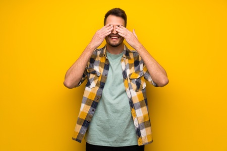 Handsome man over yellow wall covering eyes by hands. Surprised to see what is ahead