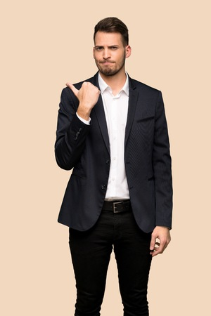 Handsome business man unhappy and pointing to the side over ocher background Stock Photo
