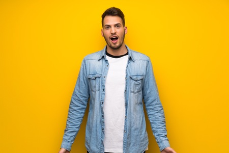 Handsome man over yellow wall with surprise facial expression