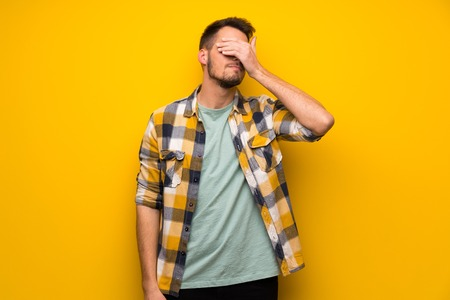 Handsome man over yellow wall covering eyes by hands. Do not want to see something Foto de archivo