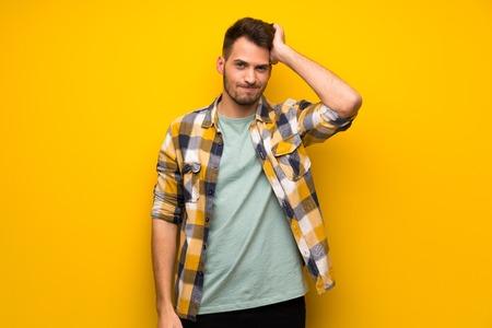 Knappe man over gele muur met een uitdrukking van frustratie en niet begrijpend