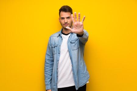 Schöner Mann über gelber Wand, der eine Stopp-Geste macht, die eine Situation leugnet, die falsch denkt