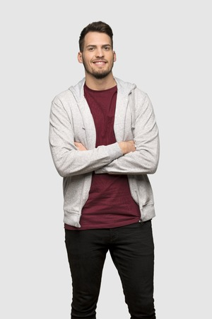 Man with sweatshirt keeping the arms crossed in frontal position over grey background