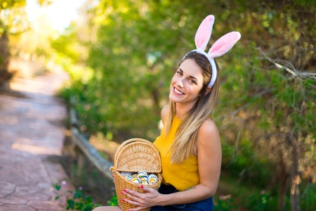 Young woman wearing bunny ears and with colorful Easter egg at outdoors Banque d'images - 119176414