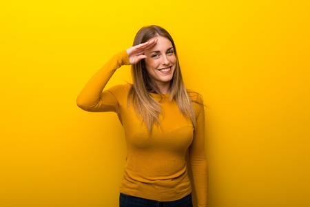 Young woman on yellow background saluting with hand Banco de Imagens