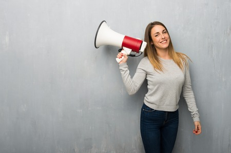 Young woman on textured wall holding a megaphone Imagens
