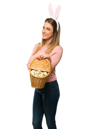Young woman wearing bunny ears for Easter holidays keeping the arms crossed in lateral position while smiling on isolated white background Stok Fotoğraf