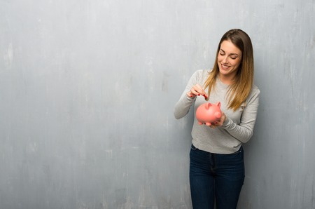 Young woman on textured wall taking a piggy bank and happy because it is full Stockfoto