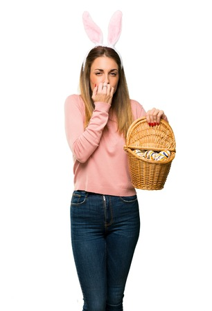 Young woman wearing bunny ears for Easter holidays is a little bit nervous and scared putting hands to mouth on isolated white background Stock Photo