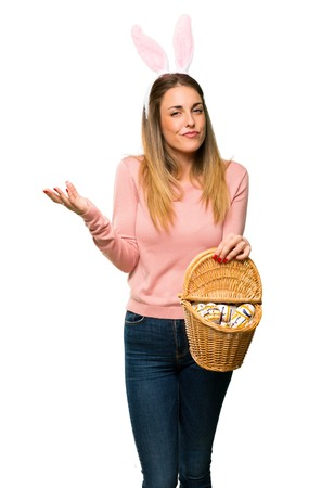 Young woman wearing bunny ears for Easter holidays having doubts and with confuse face expression on isolated white background