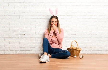 Young woman wearing bunny ears for Easter holidays covering mouth with hands